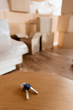 keys on table in new apartment with cardboard boxes, moving concept