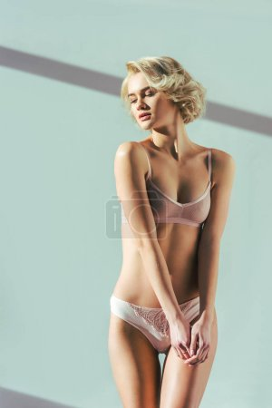 Photo for Seductive young blonde woman in pink underwear posing on grey - Royalty Free Image