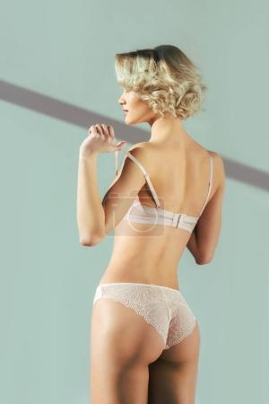 back view of beautiful sensual young woman posing in pink underwear on grey