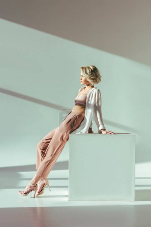 beautiful charming blonde woman in pink bra, shirt and pants sitting and looking away in studio