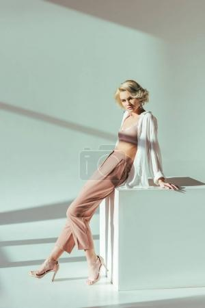 beautiful fashionable blonde woman in pink bra, shirt and pants sitting and looking at camera in studio