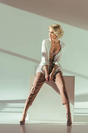 full length view of beautiful stylish blonde girl in pink bra, shirt and pants sitting and looking away in studio