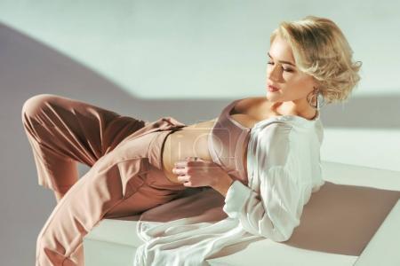 Photo pour Belle jeune femme sensuelle en soutien-gorge rose, chemise et pantalon en studio - image libre de droit