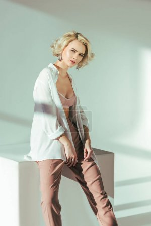 beautiful charming blonde girl in bra, shirt and pants looking at camera in studio