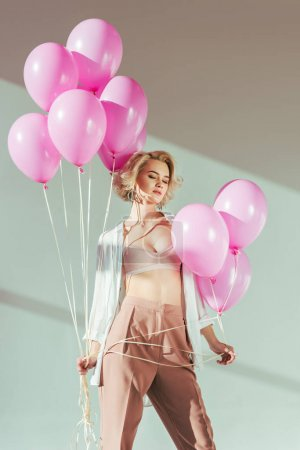 seductive young woman in trendy clothes and bra posing with pink balloons on grey