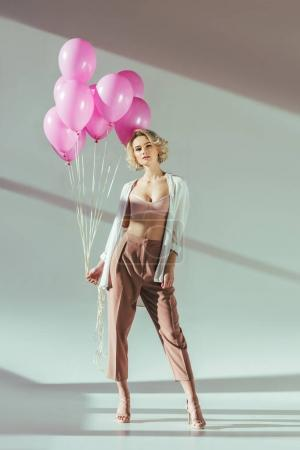 beautiful blonde woman in stylish clothes and bra posing with pink balloons and looking at camera on grey