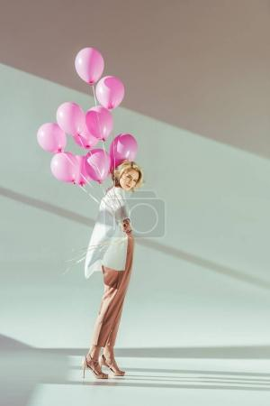 beautiful fashionable young woman holding pink balloons and looking at camera on grey