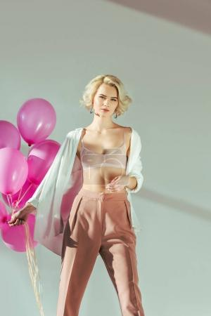 beautiful young woman in stylish clothes and bra holding pink balloons and looking at camera on grey