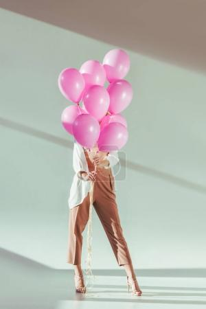 stylish young woman hiding behind pink balloons on grey