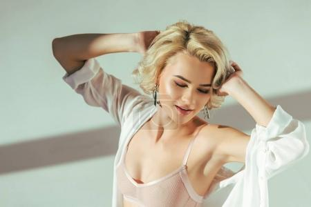 high angle view of sensual blonde girl in pink bra and shirt posing on grey