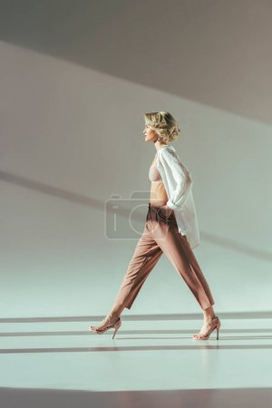 side view of stylish blonde woman in pink bra, shirt and pants walking in studio on grey