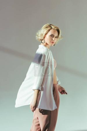 Photo for Beautiful blonde woman in pink bra, shirt and pants looking at camera on grey - Royalty Free Image