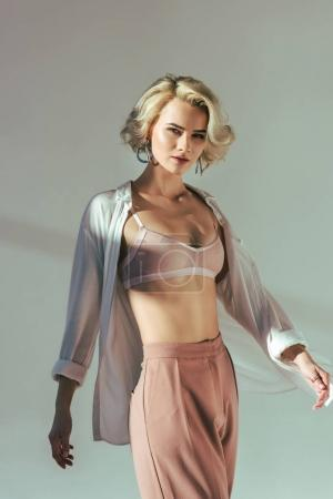 portrait of beautiful sensual woman in pink bra, shirt and pants looking at camera on grey