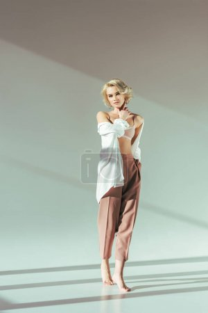full length view of beautiful barefoot blonde woman in pink bra, shirt and pants looking at camera on grey