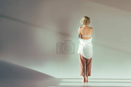 Photo for Back view of barefoot blonde girl in pink bra, shirt and pants standing in studio on grey - Royalty Free Image