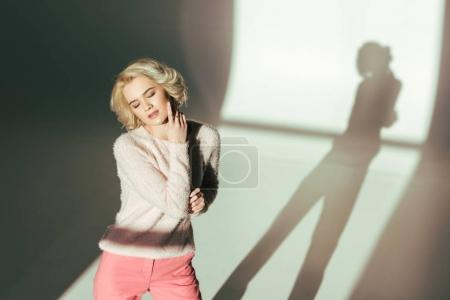 high angle view of sensual blonde girl in trendy pink clothes posing in studio