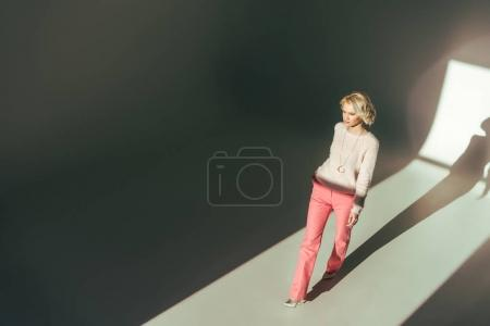 Photo for High angle view of beautiful young woman in stylish pink clothes walking in studio - Royalty Free Image