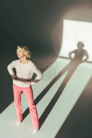 high angle view of beautiful young woman in pink clothes posing with hands on waist in studio