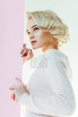 beautiful young blonde woman posing with pink placard and looking away on white