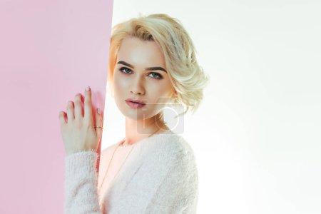 schöne junge Frau mit rosa Banner blickt in die Kamera auf weiß