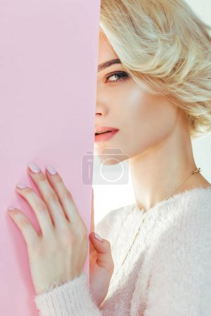 beautiful blonde girl with pink banner looking at camera on grey