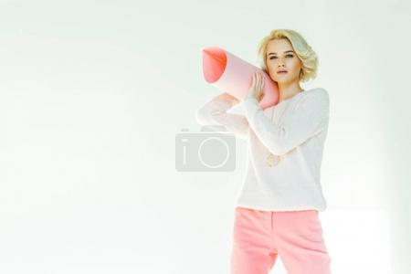 fashionable young woman holding rolled pink paper and looking at camera on grey