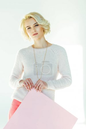 beautiful blonde girl holding pink placard and looking at camera on grey