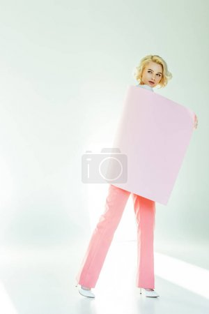Photo for Full length view of beautiful young woman posing with pink banner and looking away on grey - Royalty Free Image