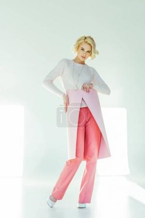 beautiful stylish blonde woman posing with pink banner and looking at camera on grey