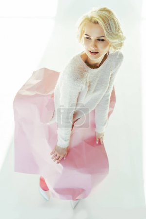 high angle view of beautiful young woman posing with pink crumpled paper on waist and looking away in studio