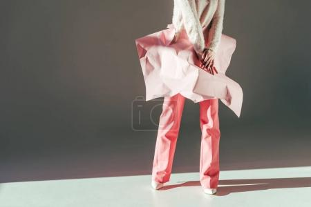 cropped shot of stylish girl posing with pink crumpled paper on waist in studio