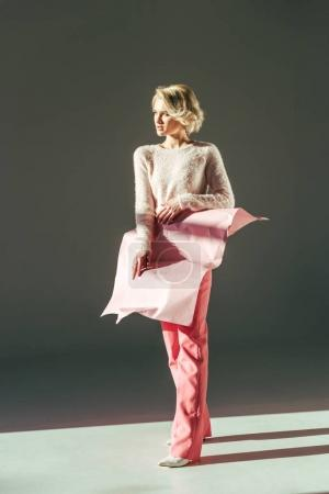 fashionable young blonde woman with pink crumpled paper on waist looking away in studio