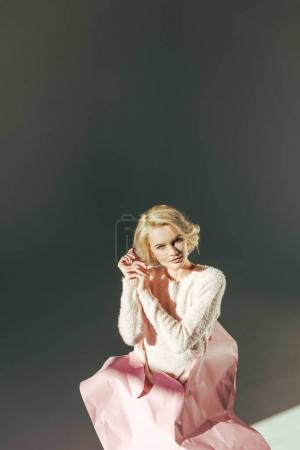 beautiful blonde woman with pink crumpled paper on waist looking at camera on grey
