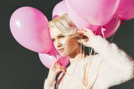 Photo pour Belle jeune femme tenant des ballons roses et à la recherche de loin isolée sur gris - image libre de droit