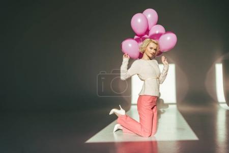 Foto de Mujer rubia elegante con globos rosa - Imagen libre de derechos