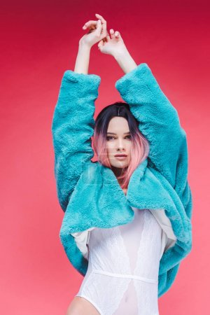 stylish girl posing in lace bodysuit and blue fur coat, isolated on pink