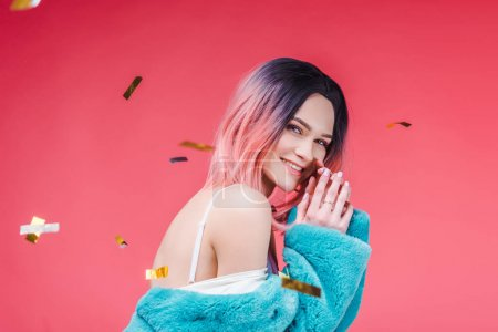 happy beautiful girl posing in blue fur coat, isolated on pink with confetti