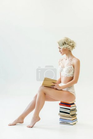 beautiful blonde girl in lace underwear reading while sitting on pile of books, isolated on white