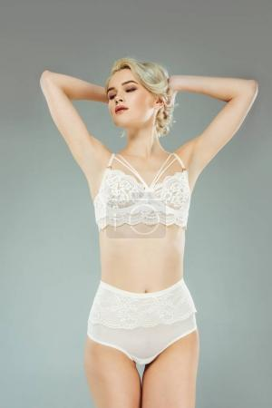 seductive blonde girl posing in sexy lace lingerie, isolated on grey