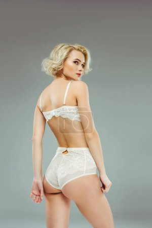 young blonde woman posing in white lace lingerie, isolated on grey
