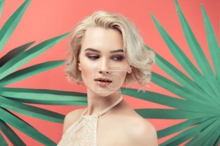 portrait of blonde woman in lace bra, isolated on red with palm leaves