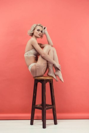 Photo for Beautiful girl in white lace lingerie sitting on stool, on red - Royalty Free Image