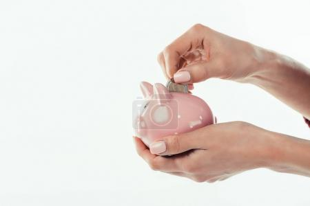 Photo for Cropped view of woman putting coin into little piggy bank, isolated on white - Royalty Free Image
