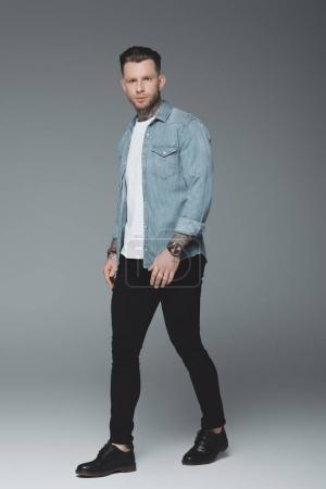 full length view of handsome young tattooed man walking and looking at camera on grey