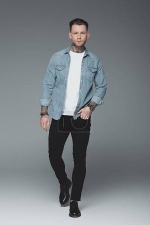 Photo pour Vue pleine longueur de beau jeune homme tatoué marchant avec la main dans la poche et regardant la caméra sur gris - image libre de droit