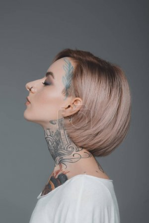 profile portrait of beautiful tattooed girl with closed eyes isolated on grey