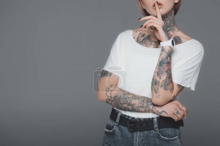Photo pour Plan recadré de jeune femme tatouée gesticulant pour le silence isolé sur gris - image libre de droit