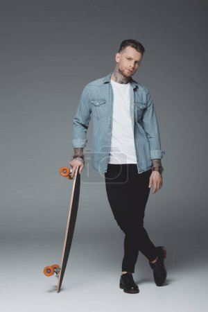 full length view of stylish young tattooed man standing with skateboard and looking at camera on grey