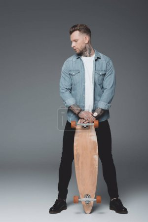 Photo for Full length view of stylish young tattooed man standing with skateboard on grey - Royalty Free Image