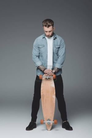 full length view of handsome young tattooed man standing with skateboard on grey